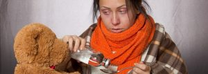 Woman wrapped up in warm clothes taking a spoon of medicine