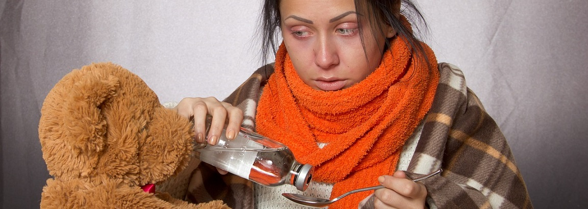 A woman wrapped in a scarf taking some flu medicine